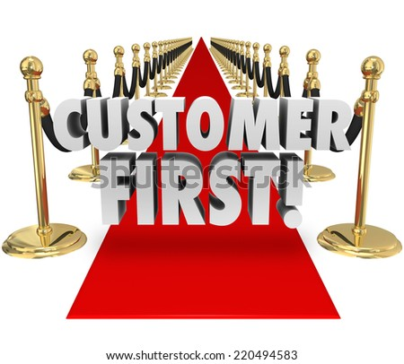 Customer First words on a red carpet to illustrate importance of placing priority on client service and support as the most critical task - stock photo
