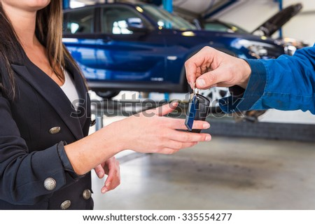 Customer gets the carkeys from mechanic after the maintanace of her vehicle - stock photo