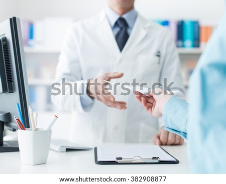 Customer giving a medical prescription to the pharmacist, treatment and healthcare concept - stock photo