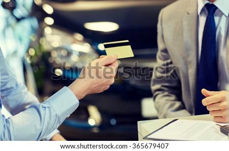 customer giving credit card to car dealer in salon - stock photo