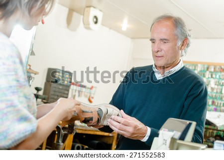 Customer giving shoe to cobbler - stock photo