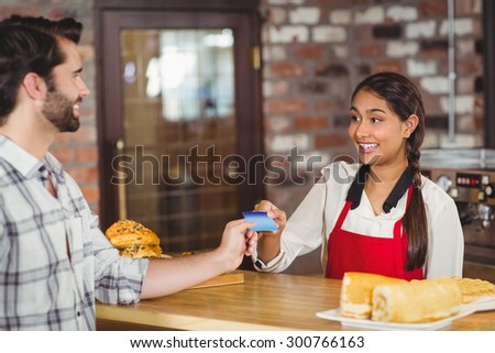 Customer handing a credit card to the waitress at the coffee shop - stock photo