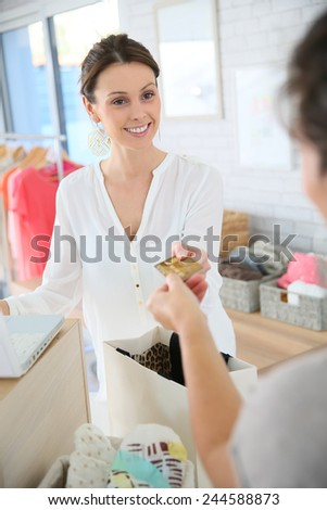 Customer in clothing store giving credit card to seller - stock photo