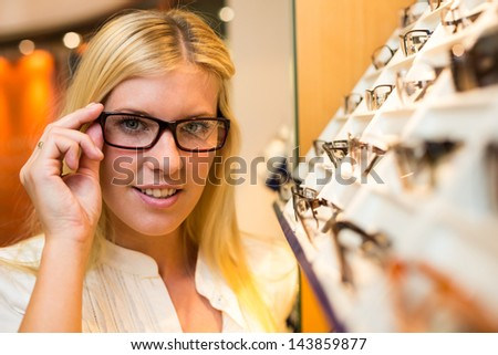 Customer in optician's shop choosing the right frame for eyeglasses from a shelf with many different models - stock photo