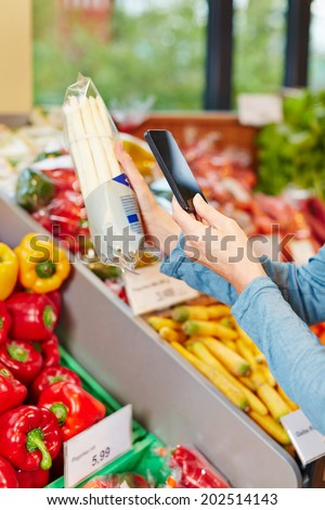 Customer in supermarket scanning barcode of a package asparagus with his smartphone - stock photo