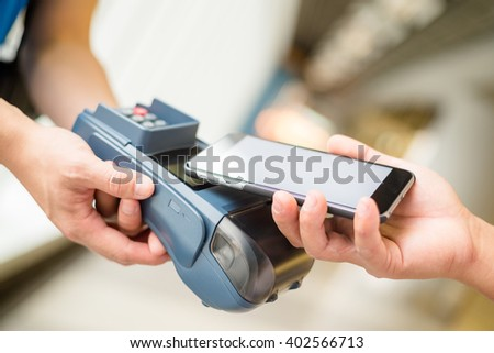 Customer pay by cellphone with NFC - stock photo