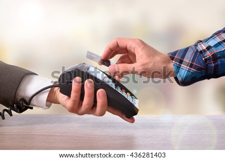 Customer paying a merchant with contactless card with NFC technology. Top view. Horizontal composition. - stock photo