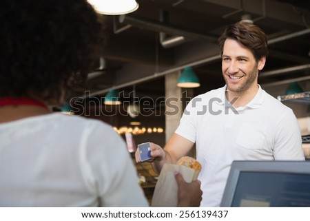 Customer paying by credit card her bread at the bakery - stock photo