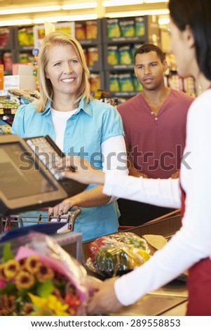 Customer Paying For Shopping At Supermarket Checkout - stock photo