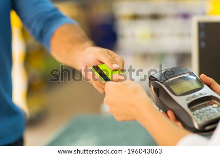 customer paying with credit card at supermarket - stock photo