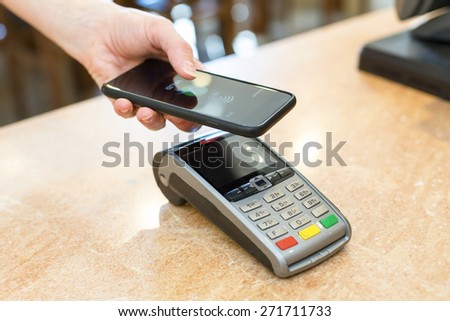 Customer paying with NFC technology - stock photo