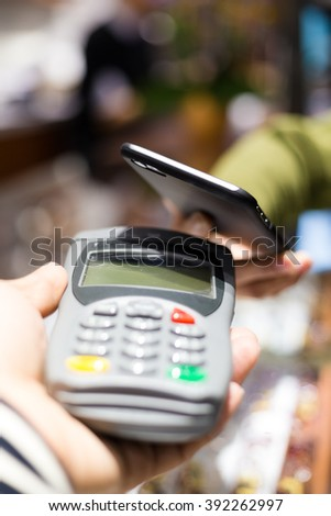 Customer paying with NFC technology on smart phone - stock photo