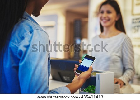 Customer paying with phone and pin pad in front of smiling cashier salesperson at store - stock photo