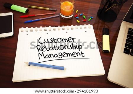 Customer Relationship Management - handwritten text in a notebook on a desk - 3d render illustration. - stock photo