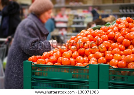 Customer select tomatoes in supermarket - stock photo