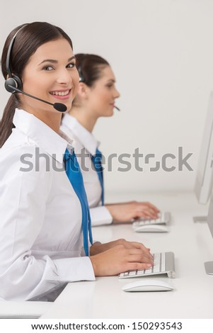 Customer service representatives at work. Two cheerful young female customer service representatives in headset working at the computer and smiling - stock photo
