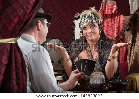 Customer showing happy tarot cards to fortune teller - stock photo