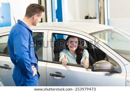 Customer showing thumbs up to camera at the repair garage - stock photo