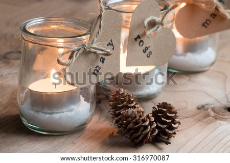 Customized eco candle holders with jars and paper labels printed for a Christmas dinner - stock photo