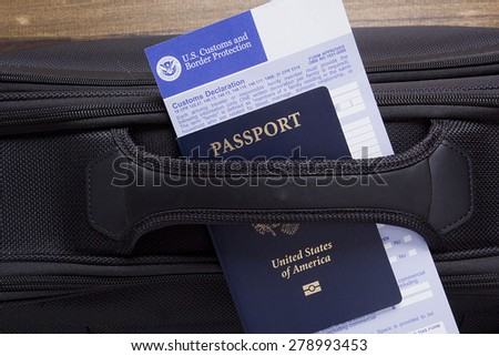 Customs declaration and passport lie on the road suitcase, passing visa control. - stock photo