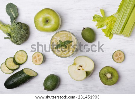 Cut and whole green colored fruits and vegetables on the white wooden table, top view - stock photo