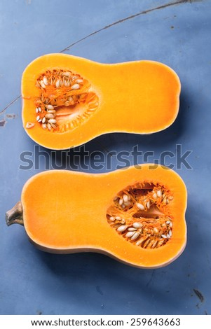 Cut butternut squash over blue metal background. Top view. - stock photo