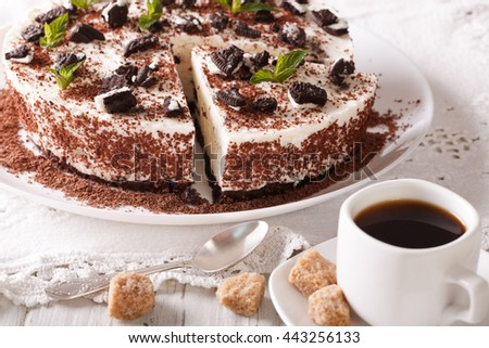 Cut cheese cake with pieces of chocolate cookies and coffee close-up on the table. horizontal