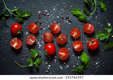 Cut cherry tomatoes on a black background with spices, top view - stock photo