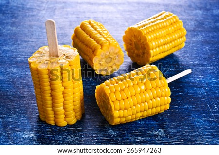 Cut corn on the cob on a stick on the blue surface - stock photo