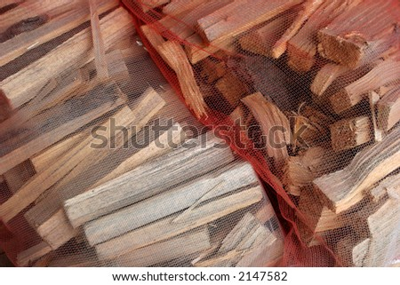 Cut firewood kindling in a net bag ready for selling. - stock photo