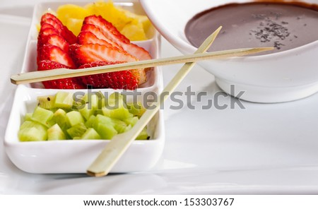 Cut fruit and molten chocolate ready to prepare a few delicious sweet skewers - stock photo