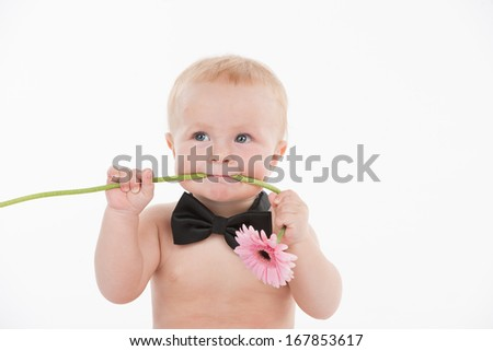 Cut funny baby boy holding flower in his mouth. Standing in bow tie isolated over white background  - stock photo
