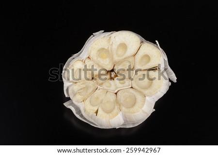 Cut garlic isolated on black background - stock photo