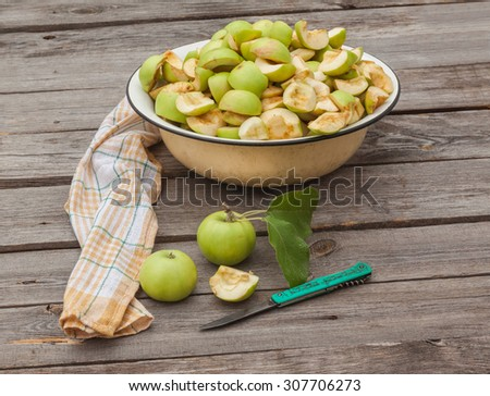 Cut into slices of apples in a bowl for jam on the wooden table - stock photo