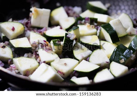 Cut into triangles zucchini fried in sauce with onions and herbs, cooking homemade dinner - stock photo