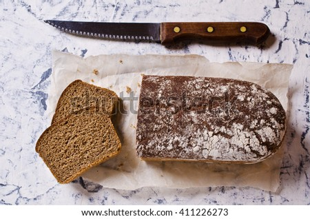 Cut loaf of rye bread on paper. Concrete background. Selective focus. - stock photo