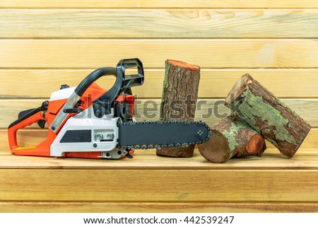 Cut logs fire wood and chainsaw isolated on wood background.  - stock photo