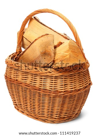 Cut logs fire wood from Silver Birch tree (Betula Pendula) in wicker basket. Renewable resource of a energy. Environmental concept. - stock photo