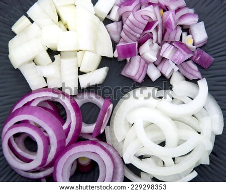 Cut onions on a black plate - stock photo