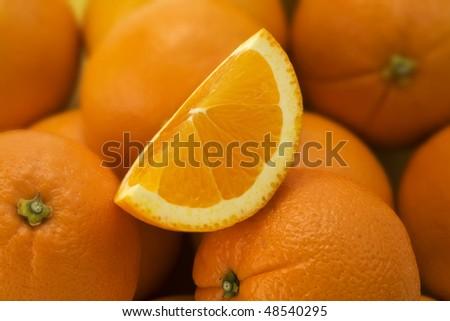 Cut Orange Quarter sitting on a pile of Oranges - stock photo