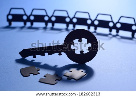 Cut out paper figures of cars and key with puzzle code - stock photo