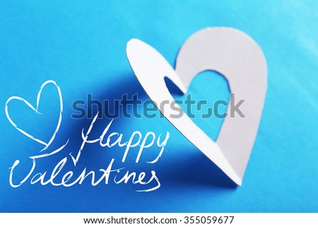 Cut out white paper heart on blue background - stock photo