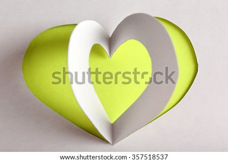 Cut out white paper heart on yellow background - stock photo
