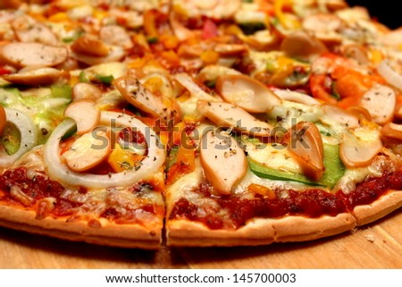 cut sausage and onion pizza on wood - stock photo
