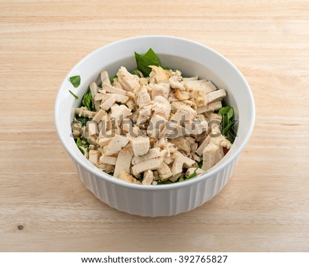 Cut up chicken breast for salad atop spinach in a bowl atop a wood table top. - stock photo
