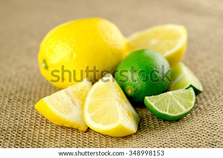 Cut up lemons and limes, sour citrus fruits - stock photo