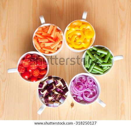 Cut vegetables of rainbow colors in white bowls - stock photo