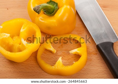 Cut yellow bell pepper with a knife on wooden cutting board - stock photo