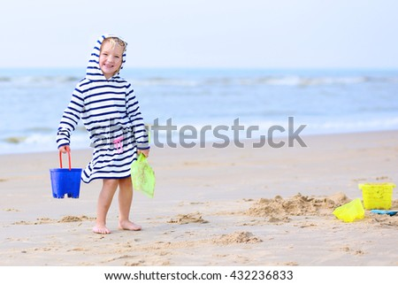 Cute active child playing on sandy beach. Happy little girl enjoying summer holidays on a sunny day. Family with young kids on vacation at the North Sea coast. - stock photo