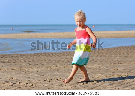 Cute active child wearing colorful dress playing on wide sandy beach. Happy little girl enjoying summer holidays on a sunny day. Family with young kids on vacation at the North Sea coast. - stock photo